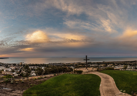 Wooden cross overlooks coastal beach town with walking path leading up to it through the grass.