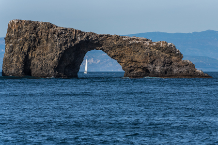 Small sailboat is visible through the Anacapa Island Arch on a sunny winter day in the Channel Islands National Park off the Pacific Ocean coast of Ventura.