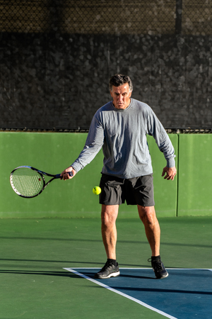 Focused recreational tennis player man keeping eyes on the ball as he prepares to hit a forehand  during a game of tennis.