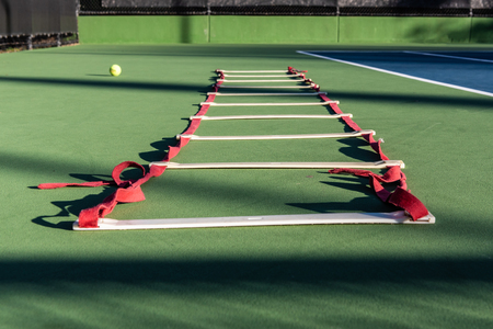 Agility ladder lying on tennis court waiting for next player to improve the footwork skills.