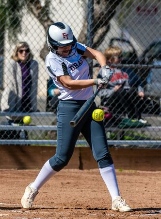 Softball player in white uniform has bat in perfect postion to hit sweet spot during game between Foothill Technology High School and Pioneer Valley on February 23, 2019.
