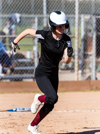 Female softball player in black uniform sprinting at top speed to first base after hit off the pitch during game.