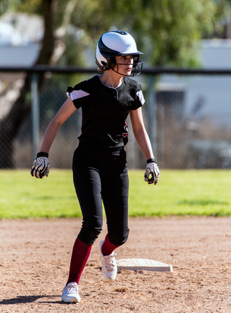Female softball player in black uniform taking an agressive lead off second base and remaining alert during game.