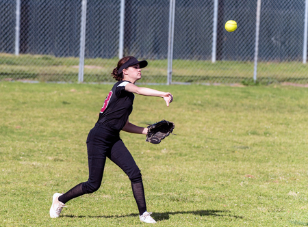 Skilled teenage softball player releasing a quick throw after making a defensive catch in the outfield.