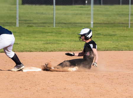 Skilled teenage softball player sliding safely into second base in a cloud of dust.