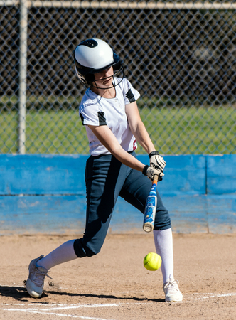 High school female softball player in white uniform making contact with ball and bat during game.