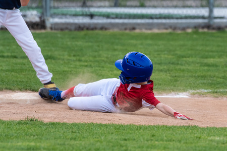 Youth baseball player in red uniform sliding safely into third base in a cloud of dust during a game.
