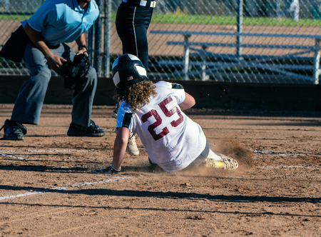 Athletic female softball player sliding safely into home plate under the legs of opponent.
