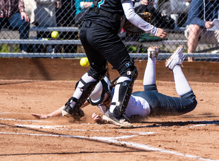 Aggressive base female base runner sliding safely into home plate as opposing catcher drops the ball.