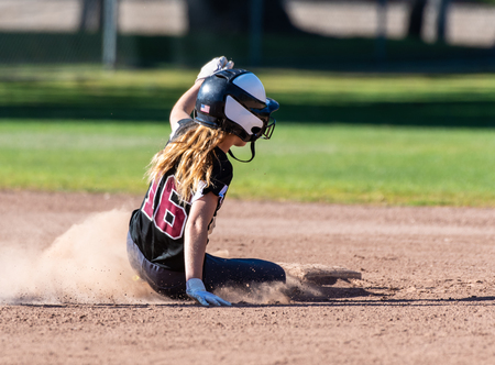 Female teenage softball player in black uniform sliding safely into second base.