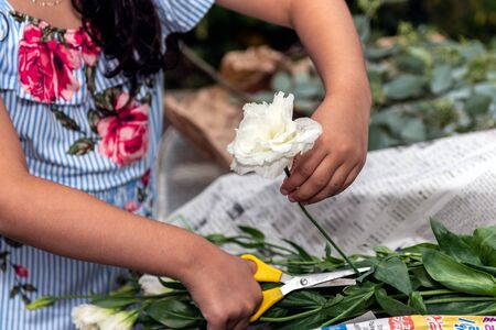 Fingers are safely holding flower stem while pruning the rose arrangement for the party gathering. 版權商用圖片