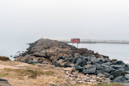 Rock jetty has a very treacherous surface and a warning sign to discourage potential climbers.