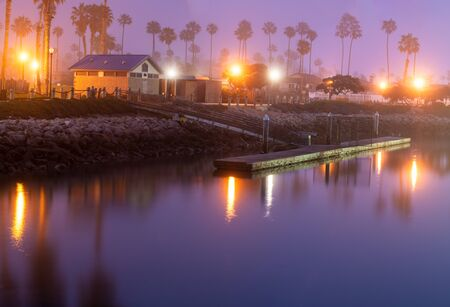 Foggy morning dims the reflecting lights on the smooth surface of the ocean cove dock water. Stok Fotoğraf