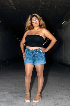 Latina female dressed in shiny, suntan pantyhose, open toe sandals, while standing in confident pose with hands on hips in dark tunnel.