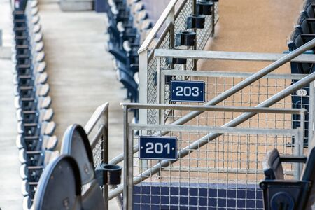 Signage marking sections 201 and 203 at baseball venue stadium between loge and field level seats.