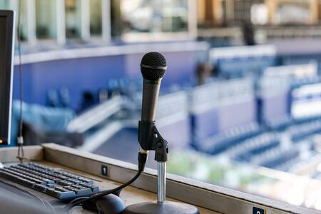 Microphone resting in holder on desk of announcers booth for baseball stadium. Imagens