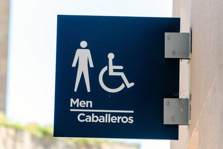 Illustrated sign with universal symbols indicating to fans where to locate the restrooms for men.