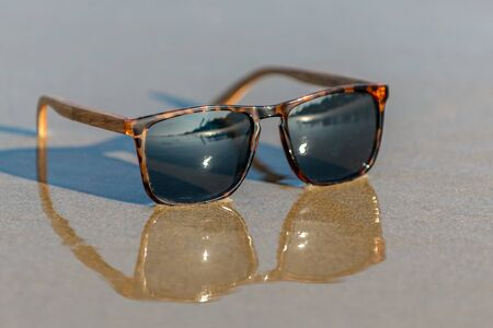 Contemporary sunglasses fashion shows leopard print style dark tinted reflective lenses reflected on wet sand of sunny beach facing camera right.