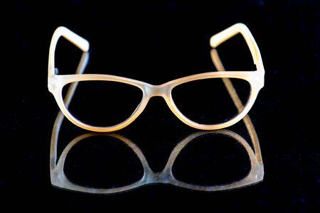 Contemporary uv protection fashion shows clear lense glasses reflected onto textured dark surface.