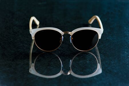 Contemporary sunglasses fashion shows aviator style dark tinted lenses reflected on dark textured surface. Imagens