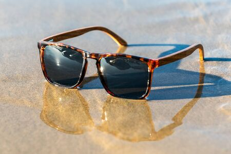 Contemporary sunglasses fashion shows leopard print style dark tinted reflective lenses reflected on wet sand of sunny beach.
