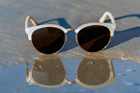 Contemporary sunglasses fashion shows aviator style dark tinted lenses reflected on wet shoreline of sunny beach.