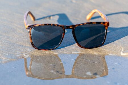 Contemporary sunglasses fashion shows leopard print style dark tinted reflective lenses reflected on wet shoreline of sunny beach. Imagens