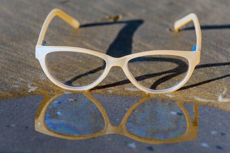 Contemporary uv protection fashion shows clear lenses reflected on wet shoreline of sunny beach.