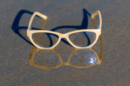 Contemporary uv protection fashion shows clear lenses reflected on wet sandy shoreline beach on sunny summer day.
