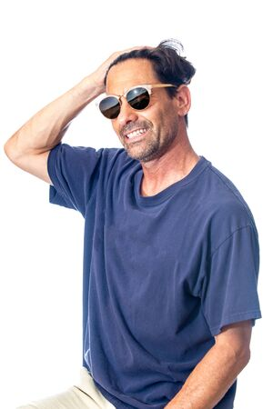 Healthy, masculine, and happy middle aged man smileing while feeling handsome wearing reflective aviator sunglasses in high key background. Imagens