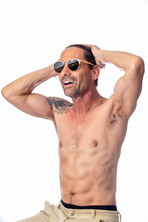Healthy, shirless, muscular, middle aged man smiling while feeling handsome wearing reflective aviator sunglasses in high key background. Imagens