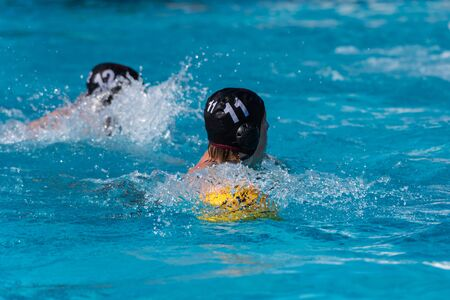 Water polo player in black uniform wearing number eleven swims with ball while looking back toward the defensive side. Imagens