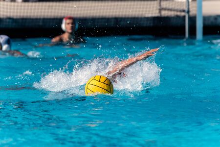 Floating water polo ball and emerging arm from submerged player while goalie looks on during competition match.