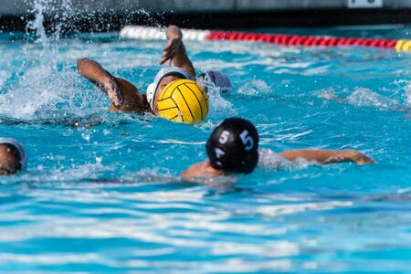 Water polo player in white uniform intently swimming while controlling ball with player in black uniform on defense.