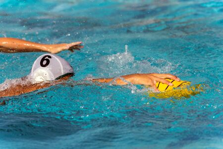Number six in the white water polo uniform reaches for the ball while face is submerged under water.