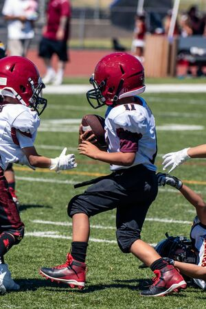 Quick and agile youth football player escapes the grasp of gloved defensive hands while running with the ball.