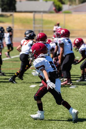 Defensive youth football player reacts to the play and quickly moves forward on the field.