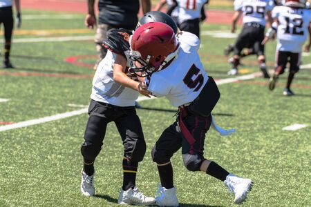 Opposing youth football players locked in each others grasp as they wrestle for dominant position.