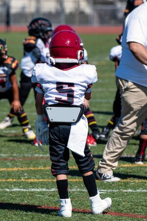 Youth football player number 5 stands on turf ready to play.