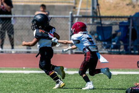Break away play on youth football game has defensive player grasping the jersey of the escaping offensive athlete. Imagens