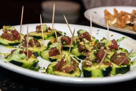 Delicious appetizer plate of cucumber slices topped with ahi poke as an hors doeuvre.