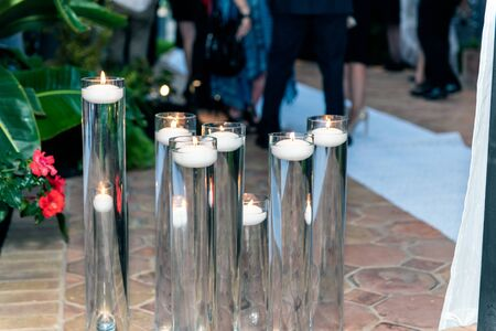 Various heights of water tubes hold outdoor floating candle decorations for the party all have glowing flames on the wicks.