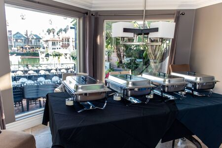 Identical chafing dishes arranged on buffet table overlooking dining tables set up outside window on waterfront deck.