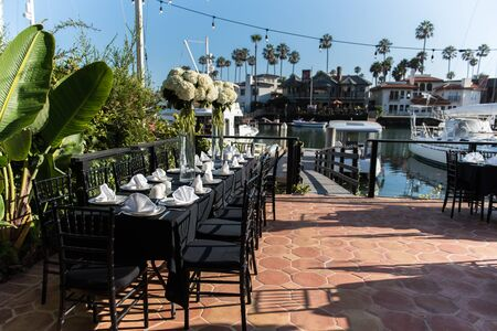 Napkins folded neatly in preparation for large group dinner event held on outdoor deck and dock leading out to canal boats. Imagens