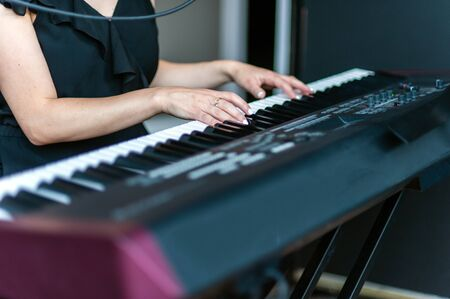 Black and white keys of the electronic piano and the skilled hands of the pianist can make magical music together.