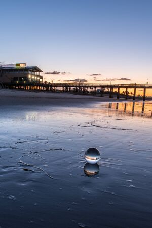 Crystal ball sphere reflects fish restaurant on top of old wooden pier as morning dawn glows in the horizon sky. Foto de archivo