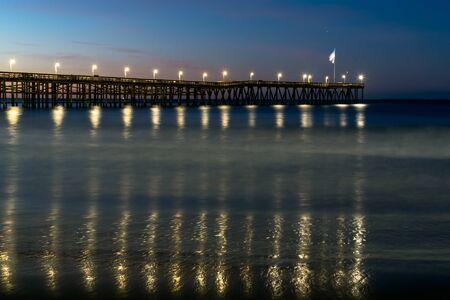 Lampenlichter, die sich im Meerwasser unter dem Ventura Pier widerspiegeln, wenn die Morgendämmerung dem Morgenhimmel Farben verleiht.