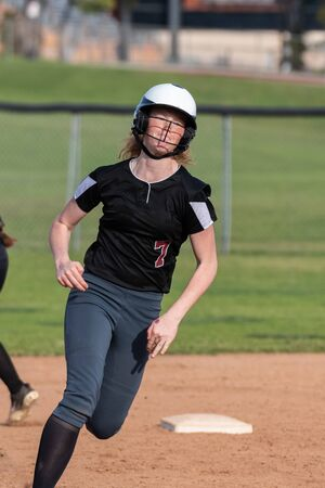 High school female softball player runs at full speed around second base with determined expression on face.
