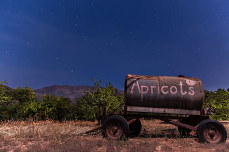 Antique farming water tank trailer illuminated by moonlight on tree orchard under Topatopa Mountain and stars in the sky.
