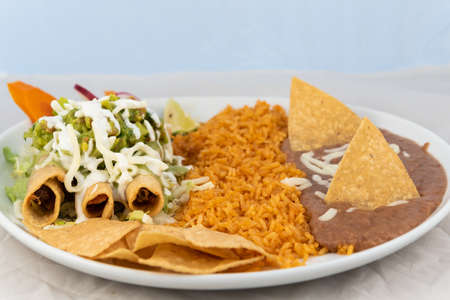 Taquitos covered in cheese with rice and beans served on a hot plate for some delicious Mexican food.